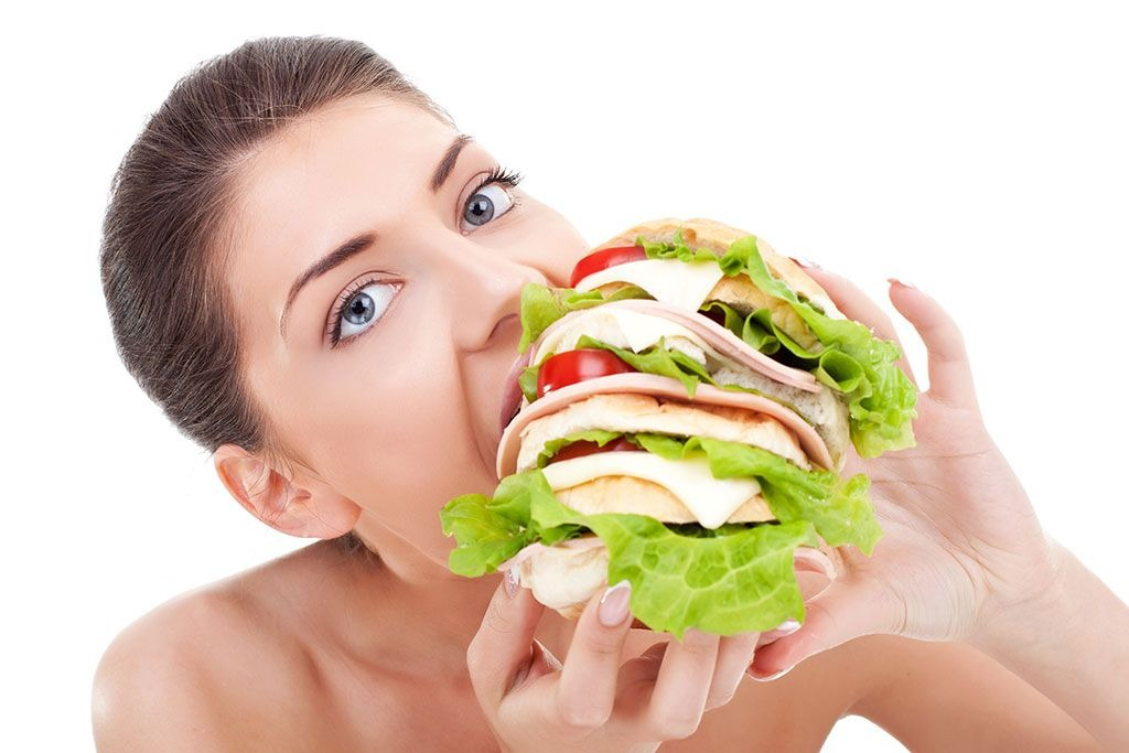 woman eating oversized sandwich - best cheat meal on cheat day