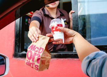 Fast food worker handing customer McDonald's ice cream sundae from drive thru