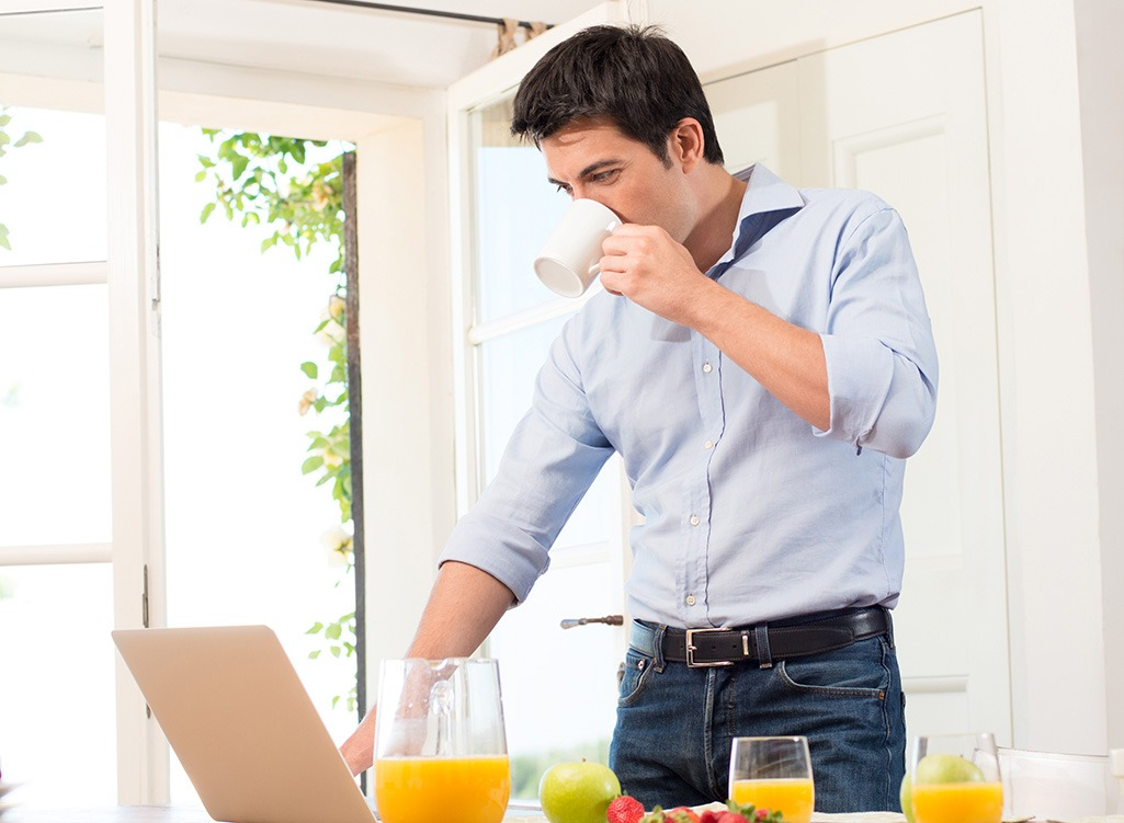 Man drinking coffee and looking at laptop