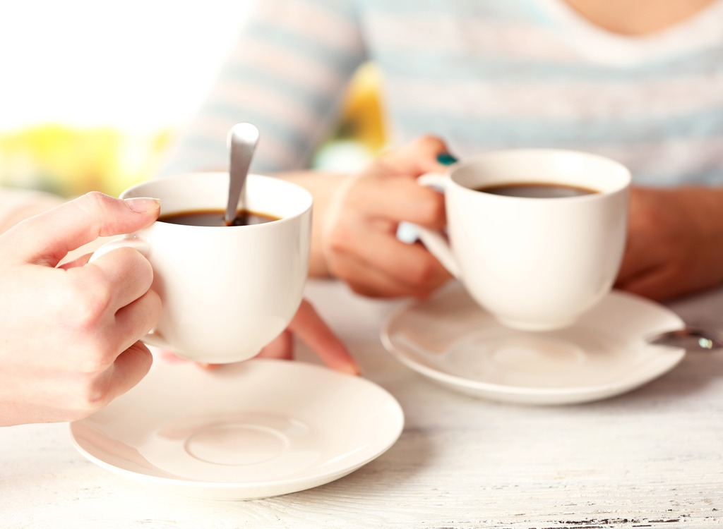 Two people holding coffee cups - foods that make you poop