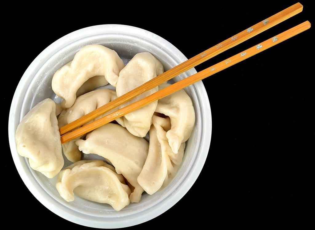 dumplings on white bowl with chopsticks