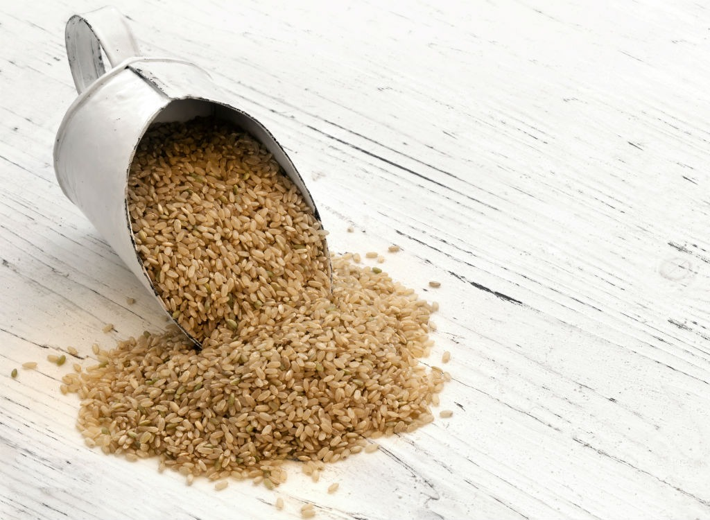 Brown rice spilling out of cup - foods that make you poop