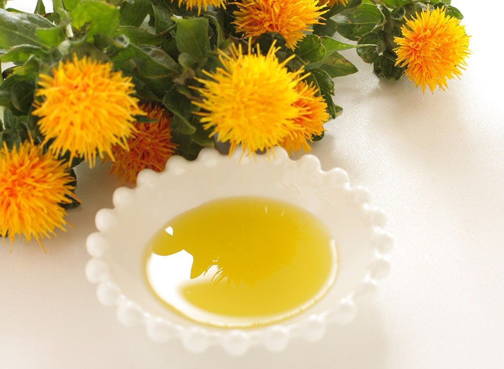 bowl of safflower oil next to plant in white dish