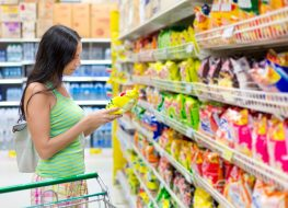 Woman shopping in supermarket snack aisle