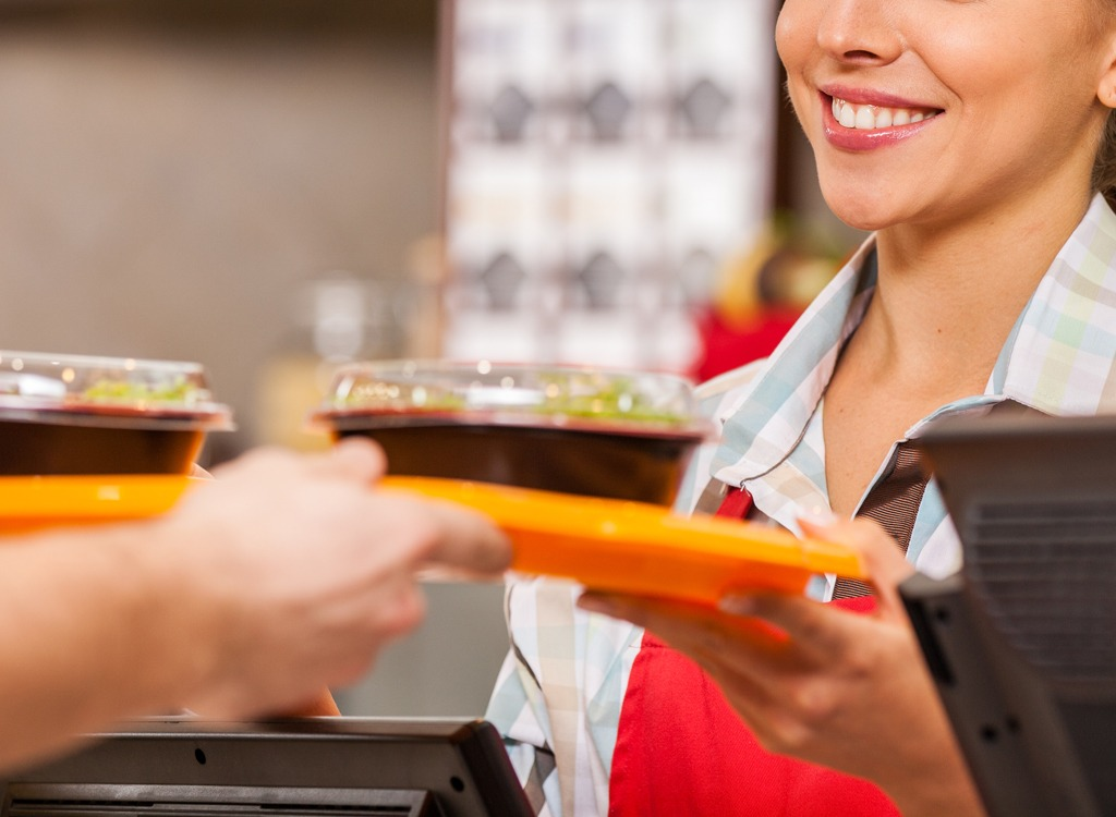 Fast food server giving customer a tray of food