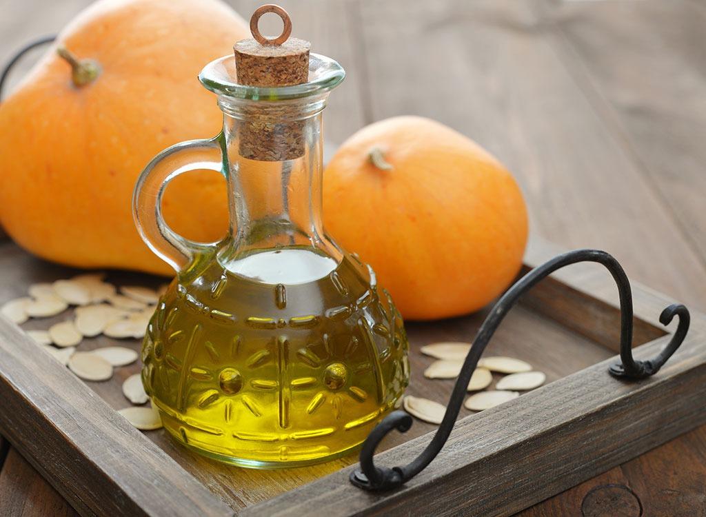 pumpkin seed oil in bottle with pumpkin seeds and pumpkins
