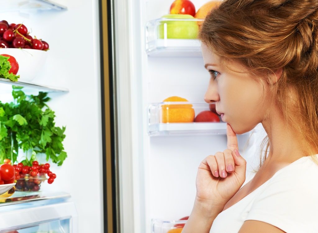 Woman looking in refrigerator - stop thinking about food