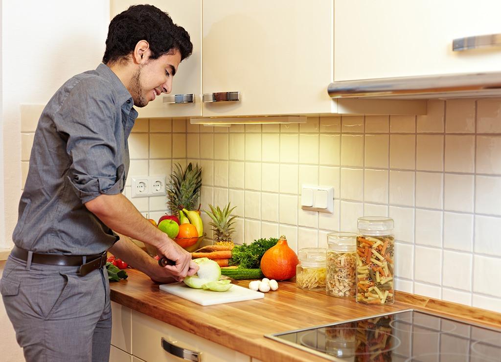 Man chopping vegetables in kitchen