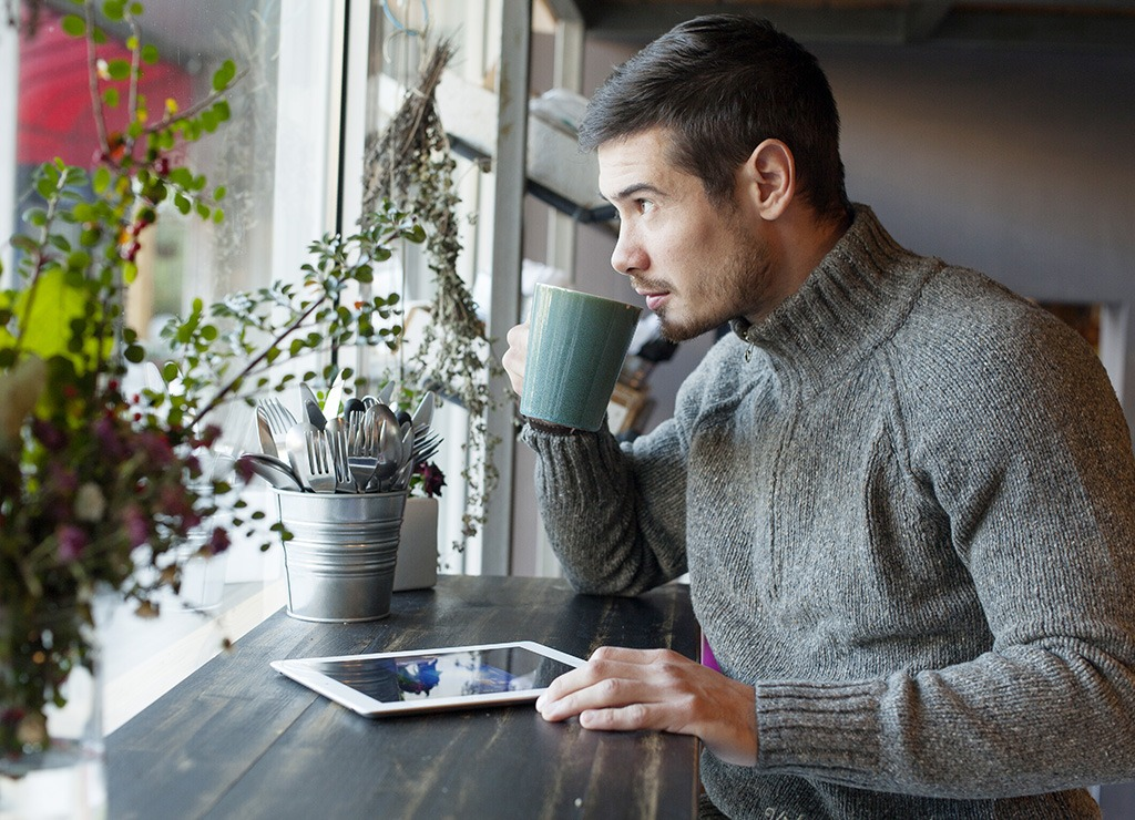Man reading tablet and drinking coffee at cafe