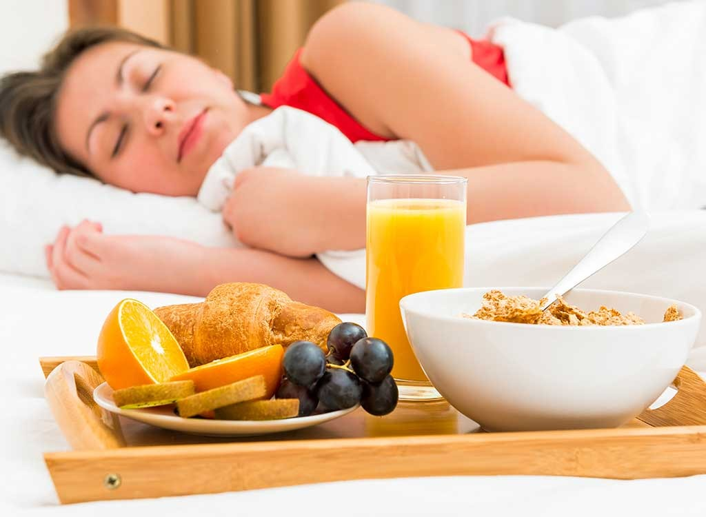 woman sleeping next to breakfast tray