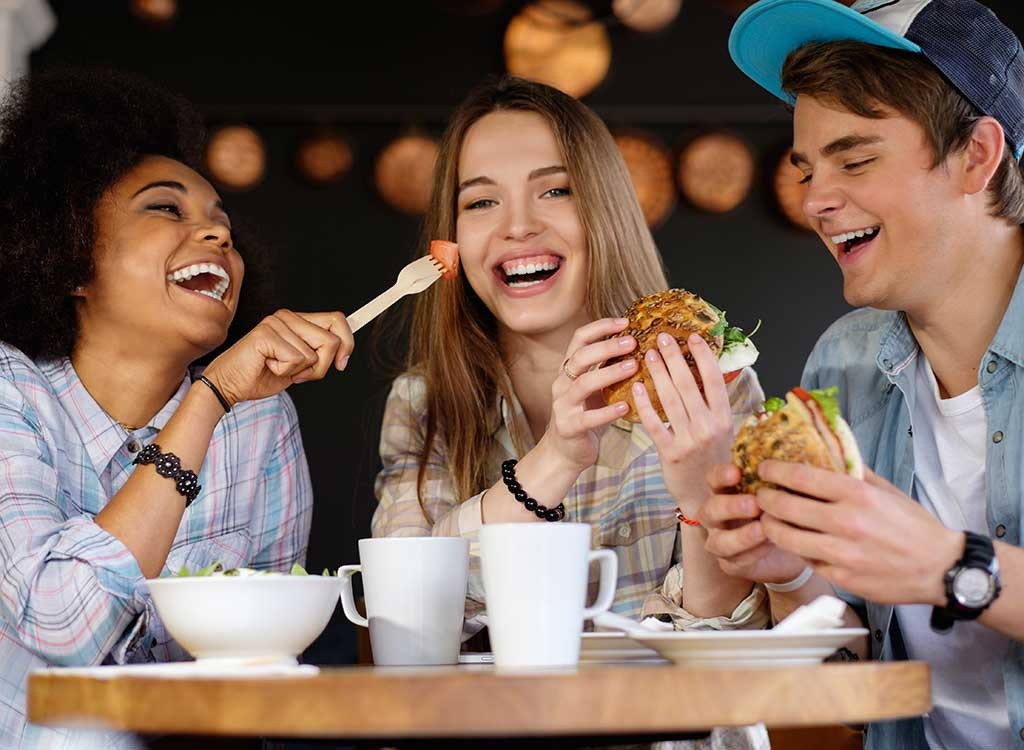 Friends laughing together while eating