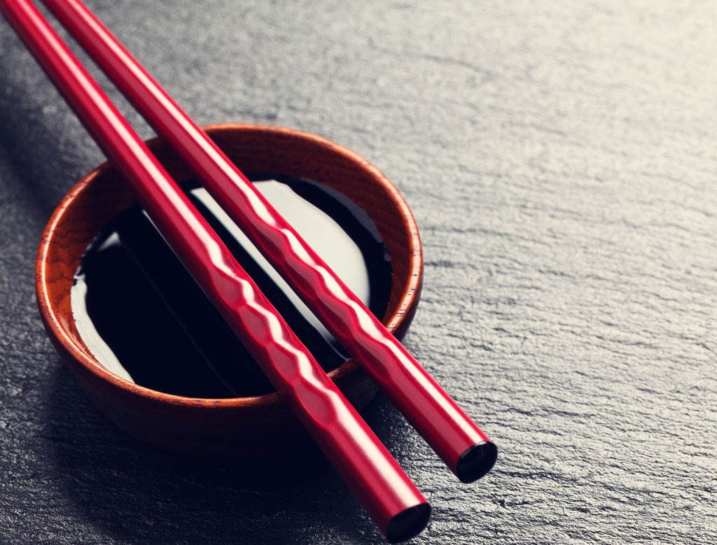 red chopsticks and bowl of soy sauce on dark background