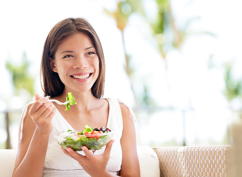 woman enjoying a salad - best cheat meal on cheat day