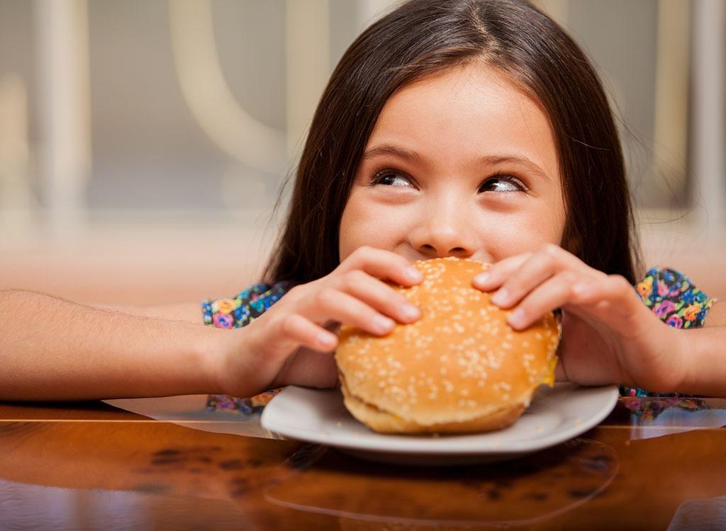 Little girl eating burger