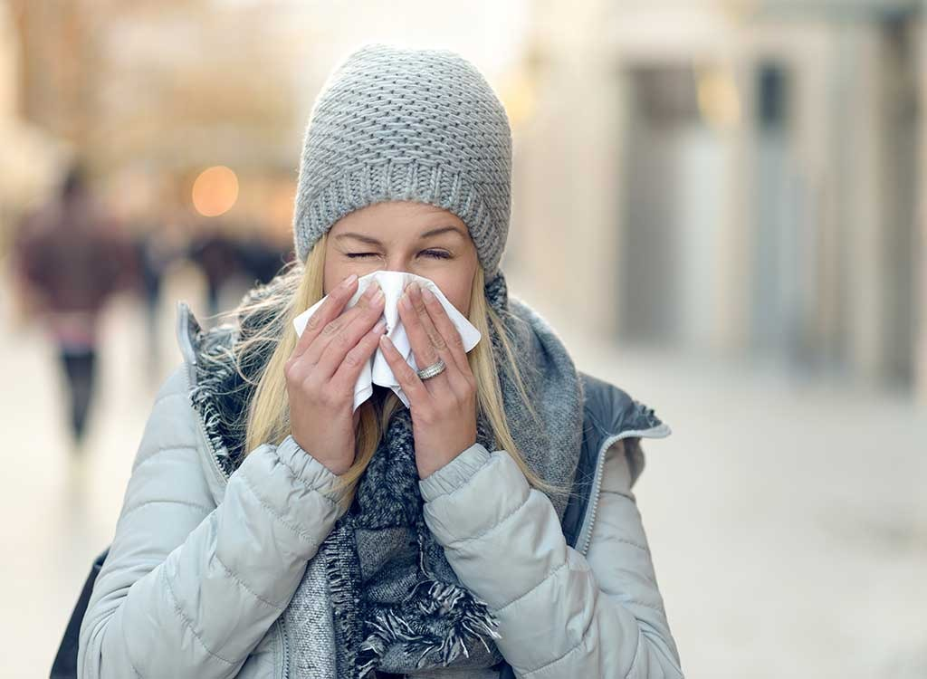 Woman with cold and sneezing
