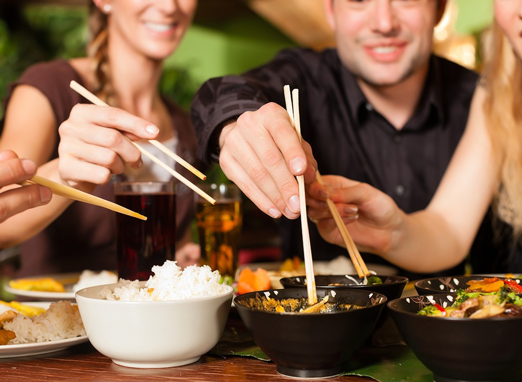 group eating with chopsticks at a chinese restaurant - best cheat meal on cheat day