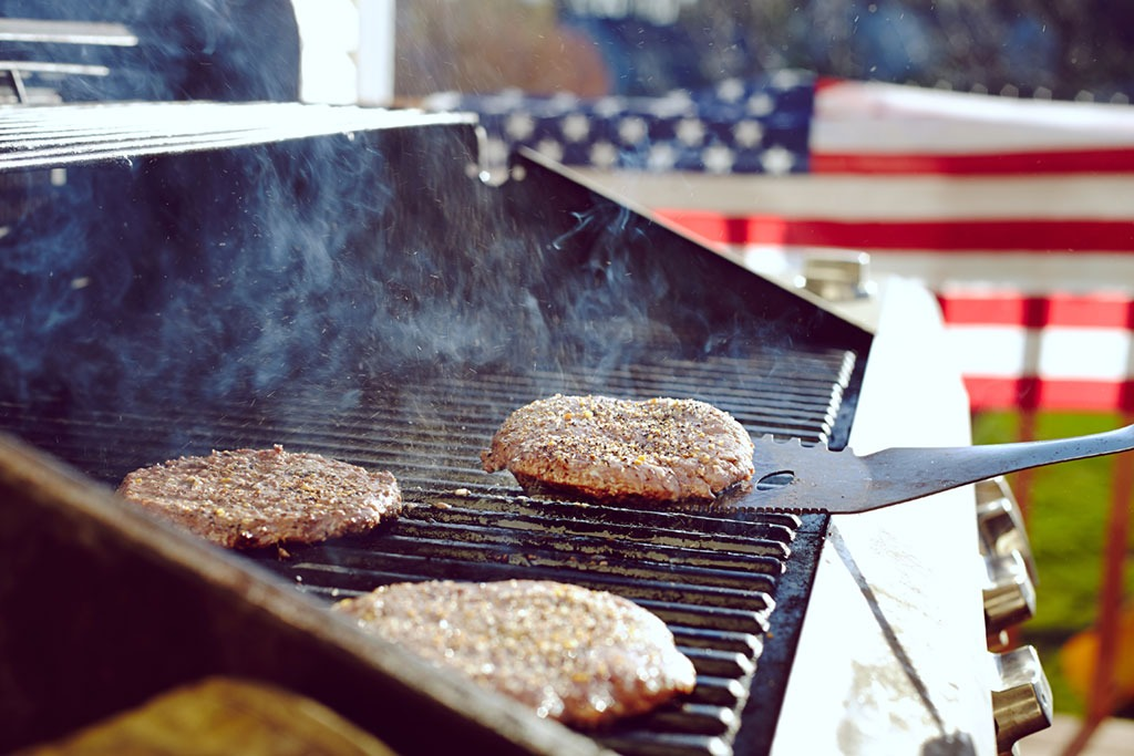 flipping burgers on grill