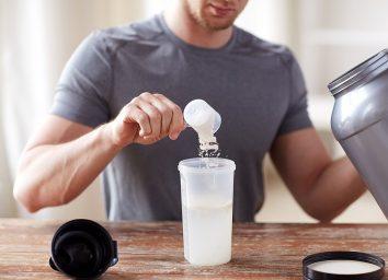 Man pouring protein powder in blender bottle