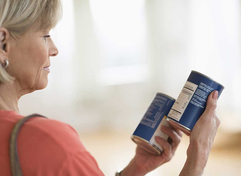 woman looking at can labels