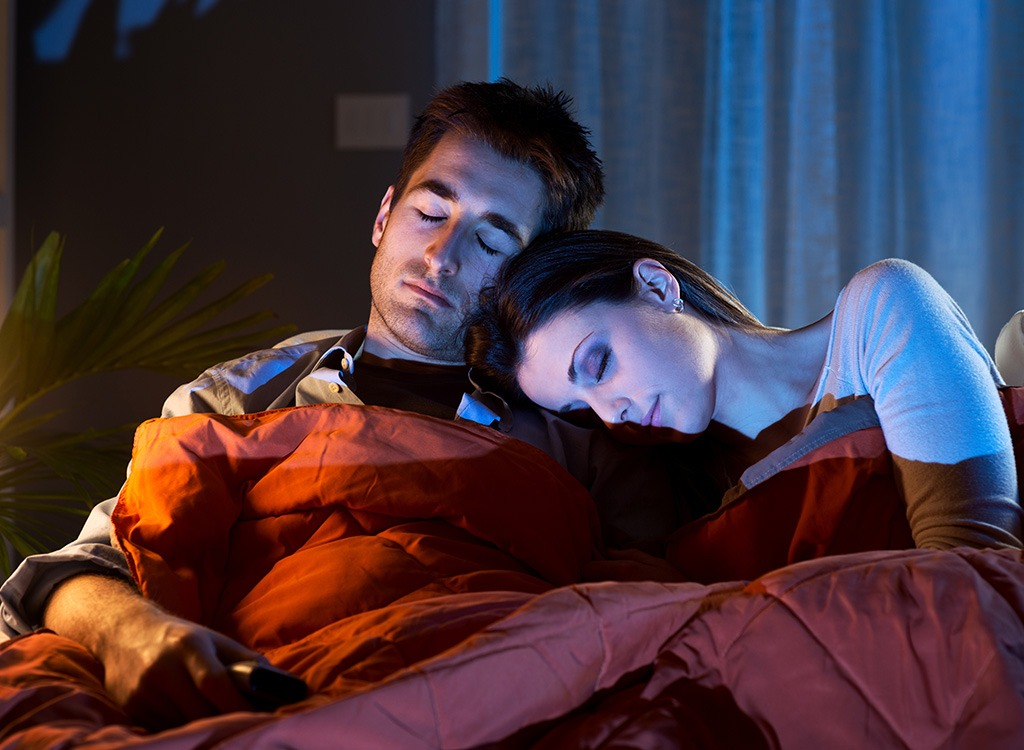 couple sleeping in front of tv