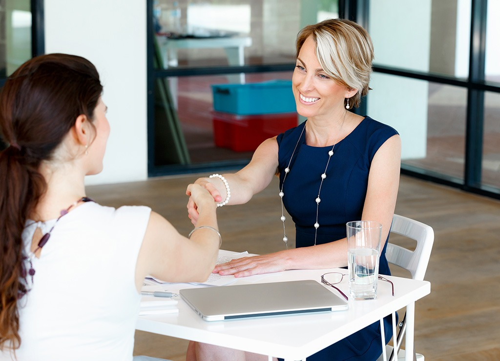 Women shaking hands at business