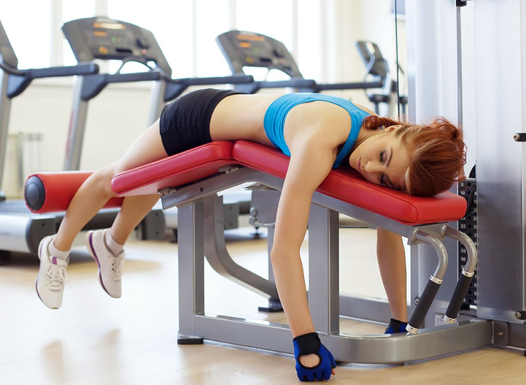 Woman tired in gym lying down on weight bench - best cheat meal on cheat day