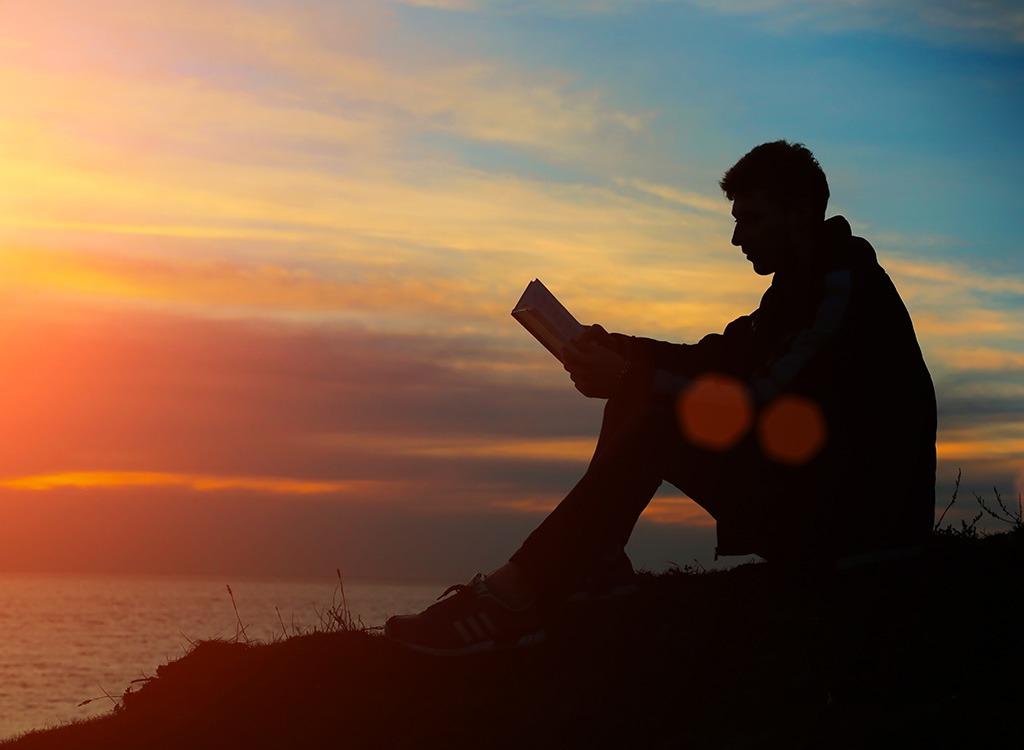 man reading at sunset