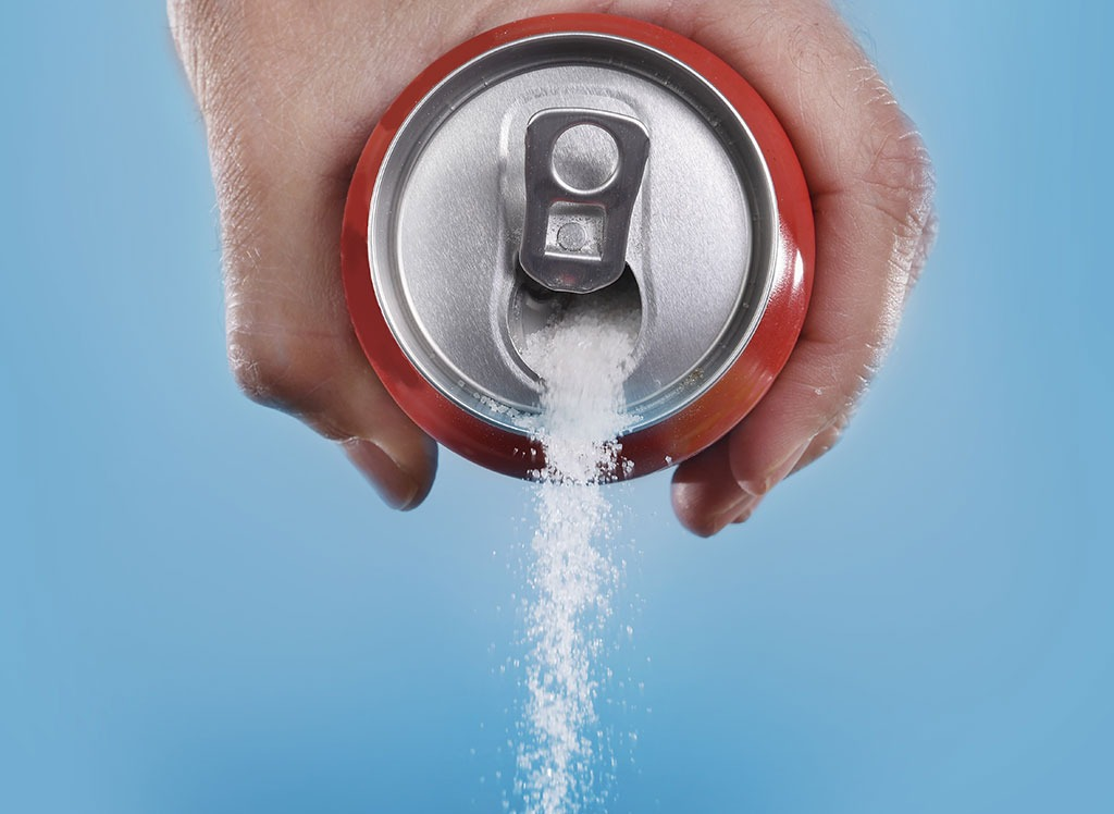 Pouring sugar out of a can of soda