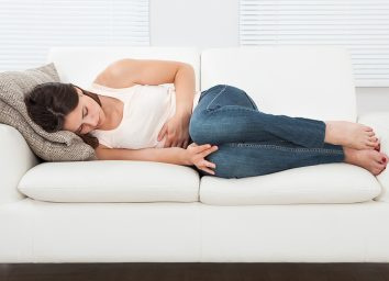 Woman holding stomach on couch