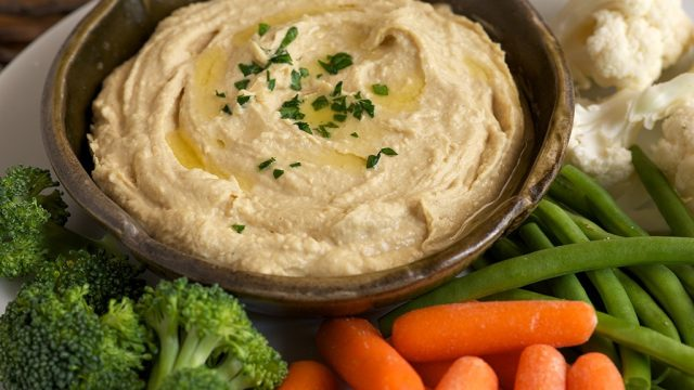 hummus in bowl served with raw vegetables