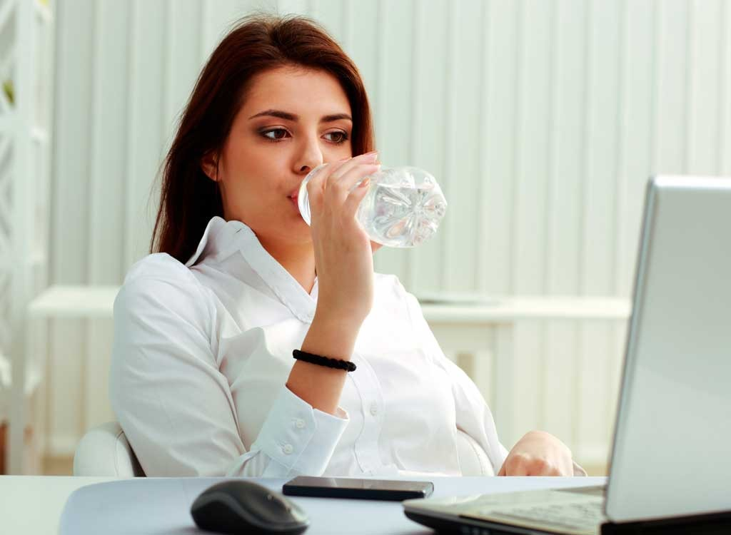 woman drinking water at desk