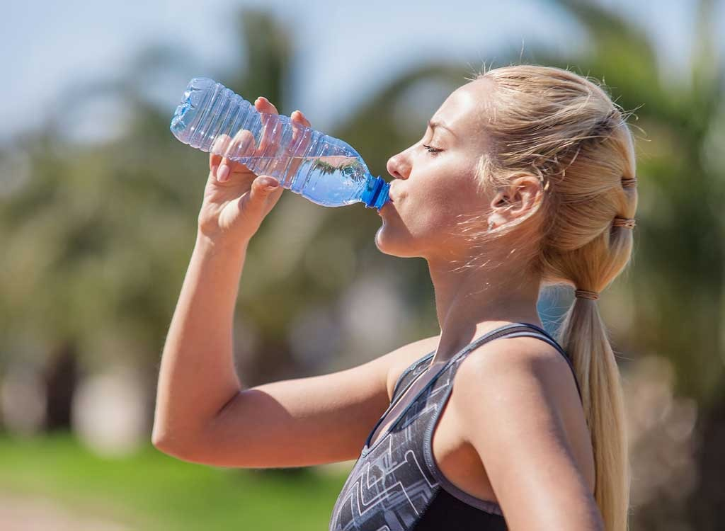 Woman drinking out of plastic water bottle