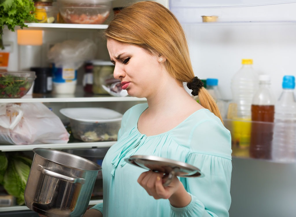 woman smelling spoiled food from pot holding lid