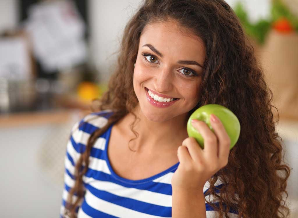 girl with long hair smiling holding a green apple