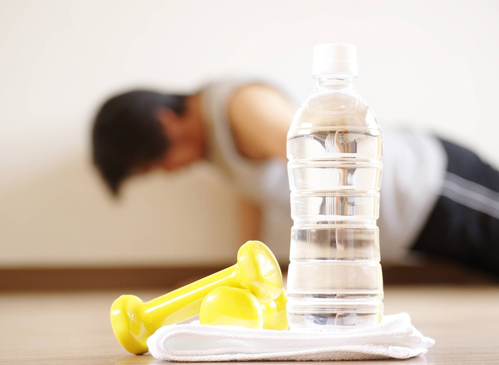 Plastic water bottle with man doing pushups in background