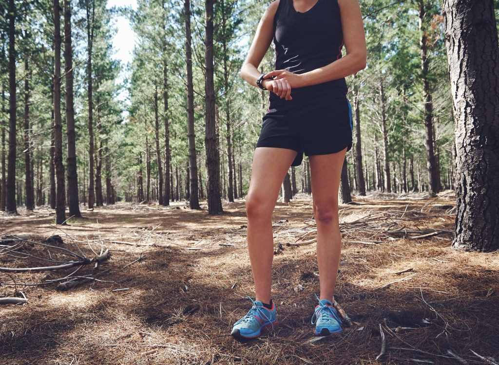 Woman timing on watch during run in woods