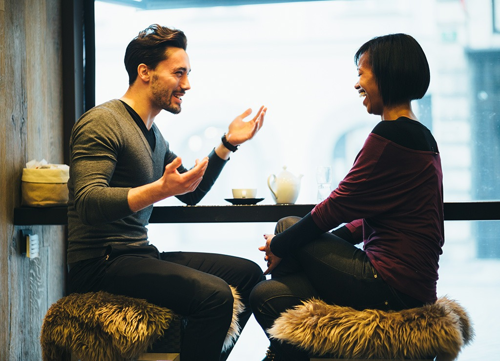 Two people having conversation at a bar