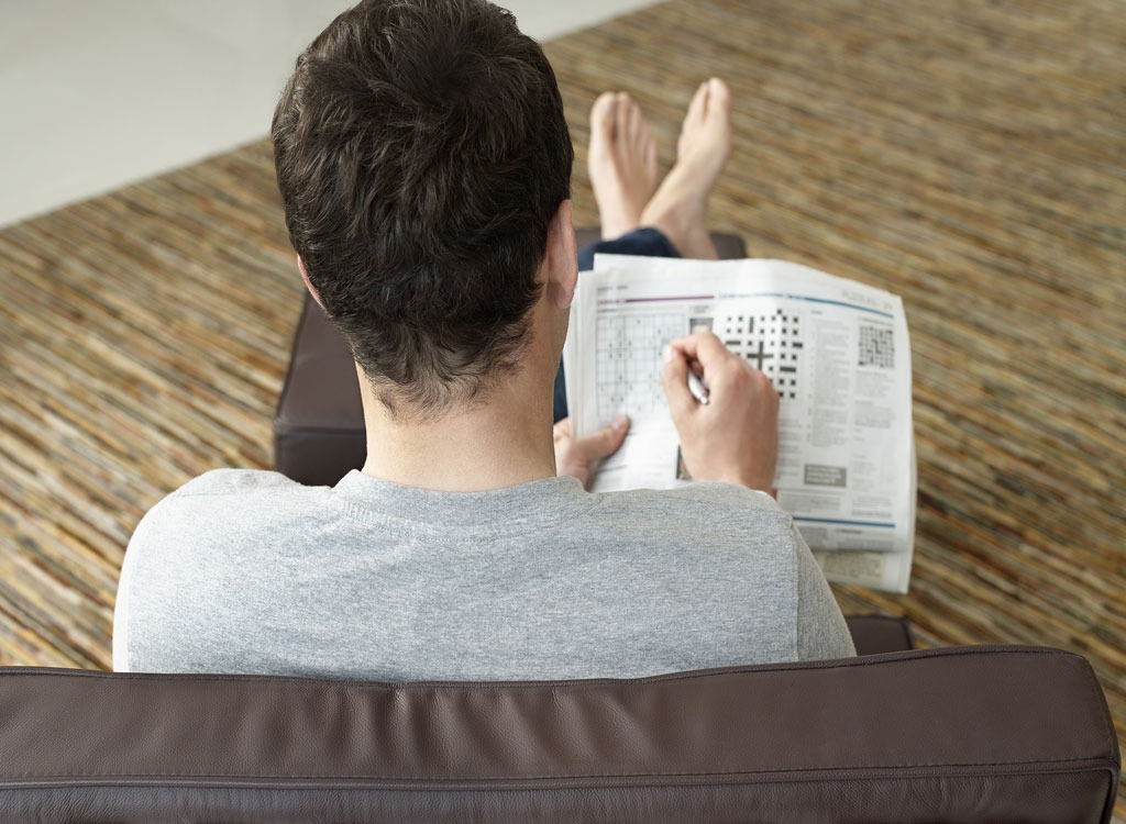 Man working on crossword puzzle