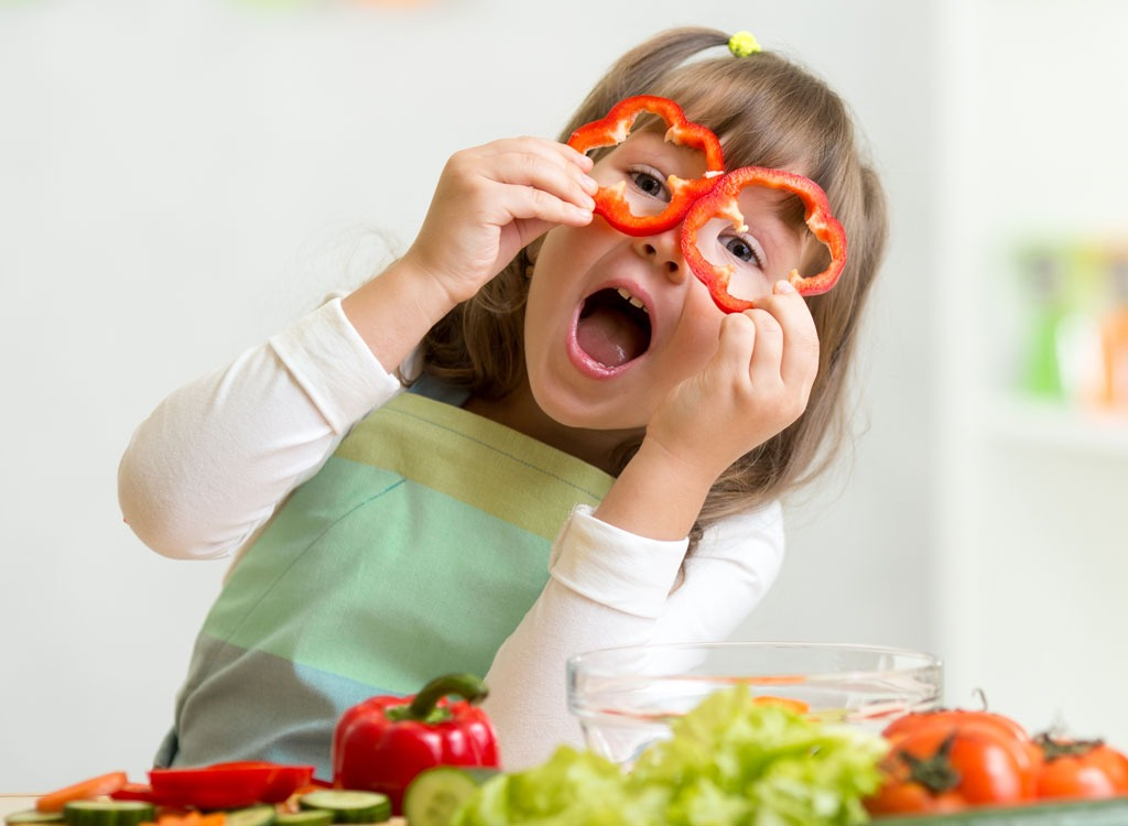Kid playing with vegetables