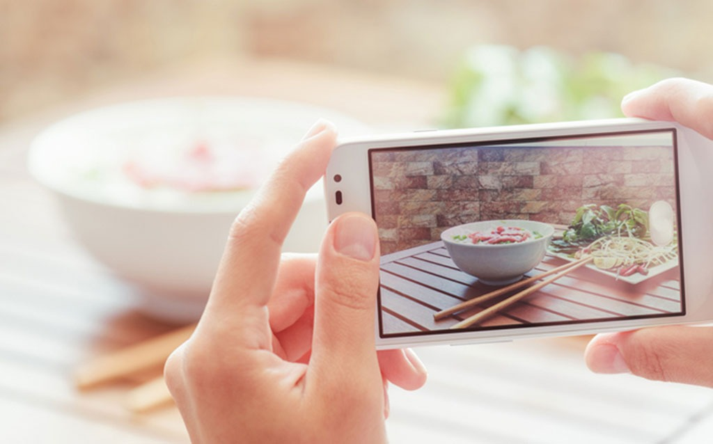 woman taking picture of meal with cellphone