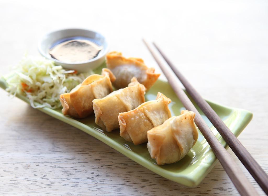 crab wonton on green plate with chopsticks