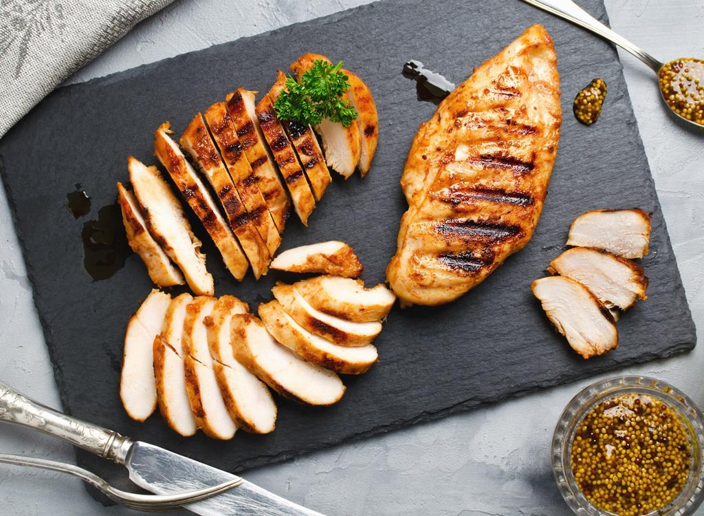 Cut up cooked chicken breast on a dark grey cutting board