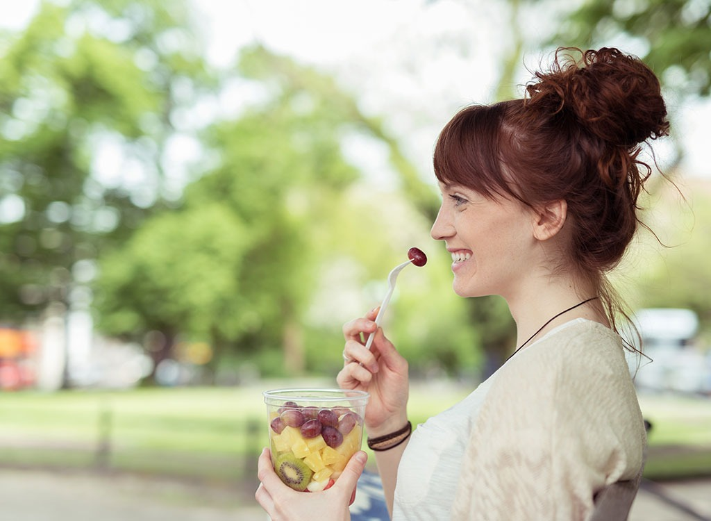 woman eating a grape - best cheat meal on cheat day