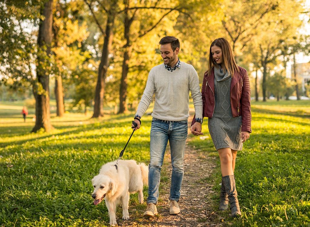 Happy couple walking dog