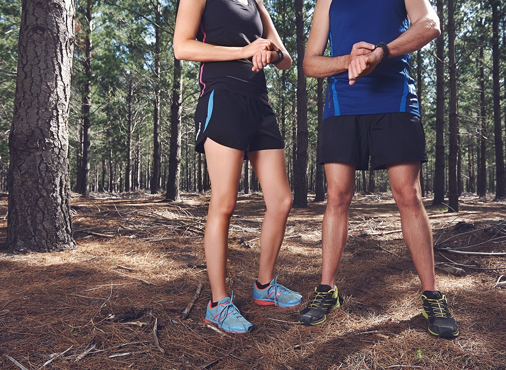 Man and woman checking fitness watches in woods during run