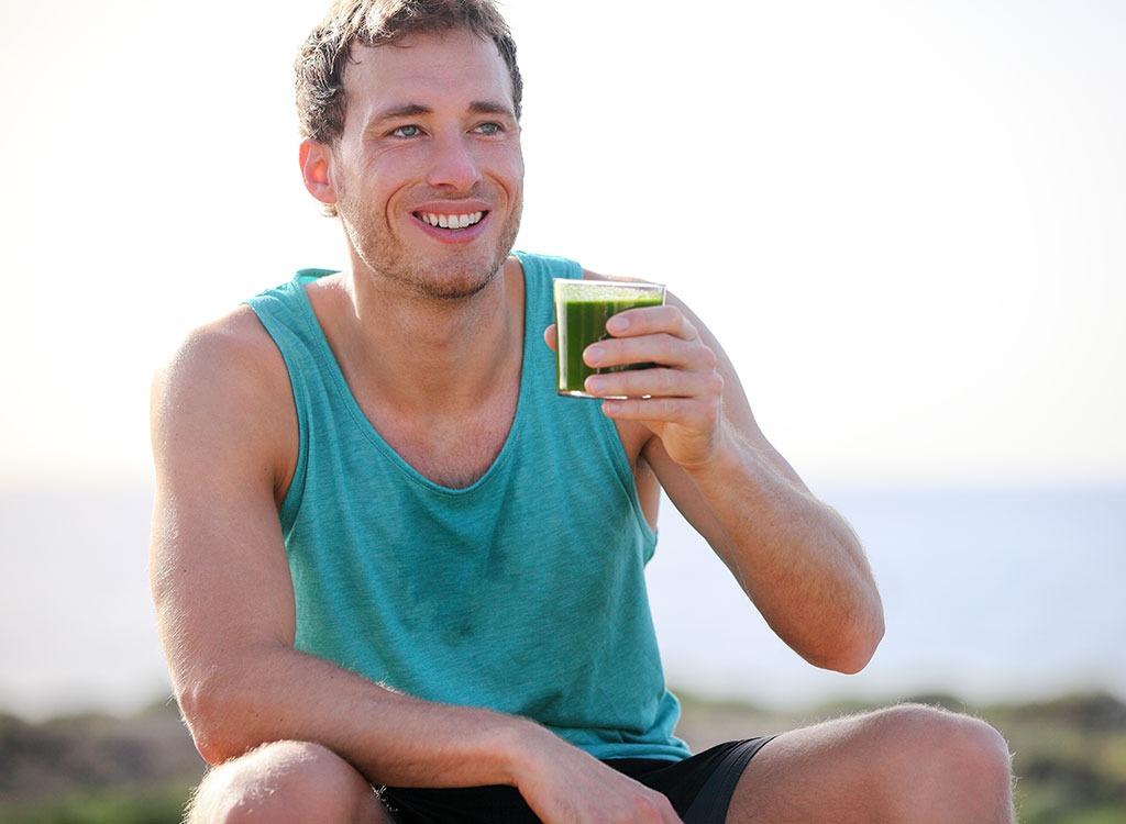 man drinking green smoothie