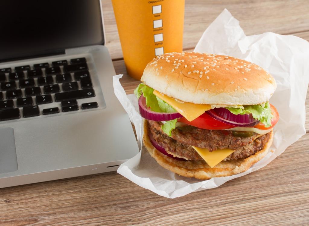 Fast food burger next to laptop