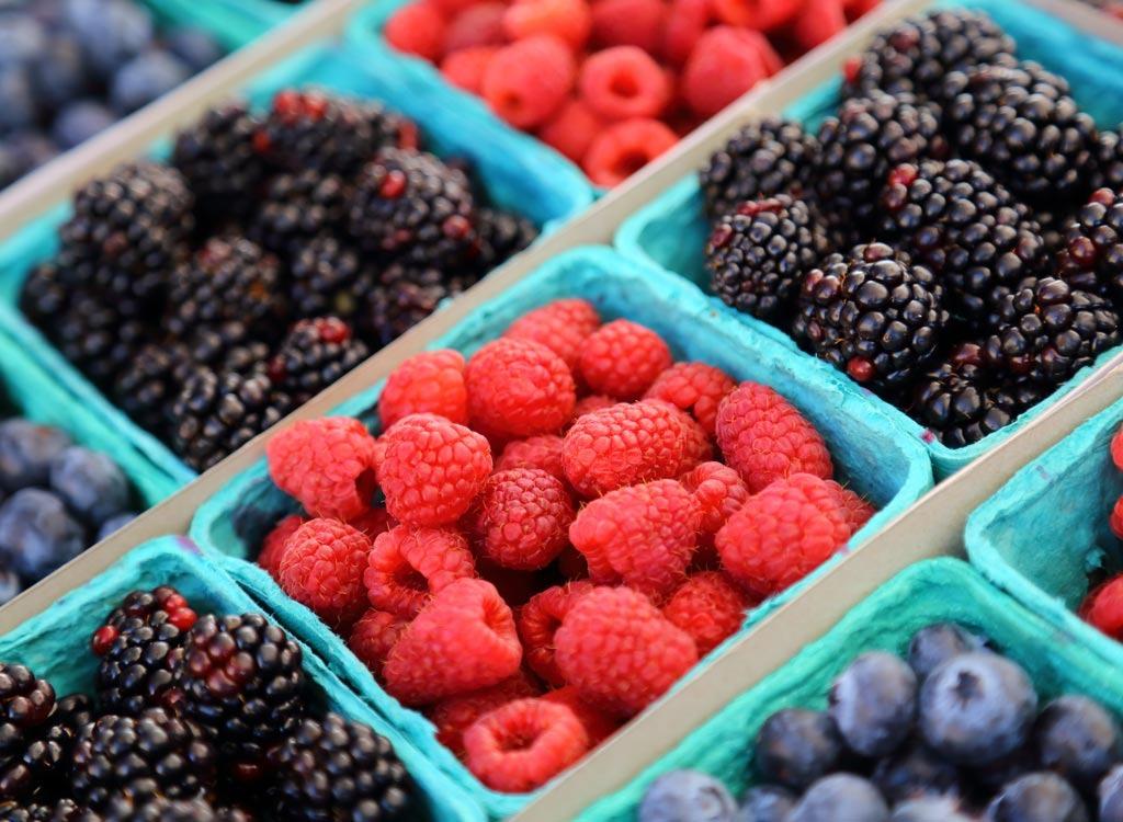 Raspberries, blueberries, and blackberries in crates