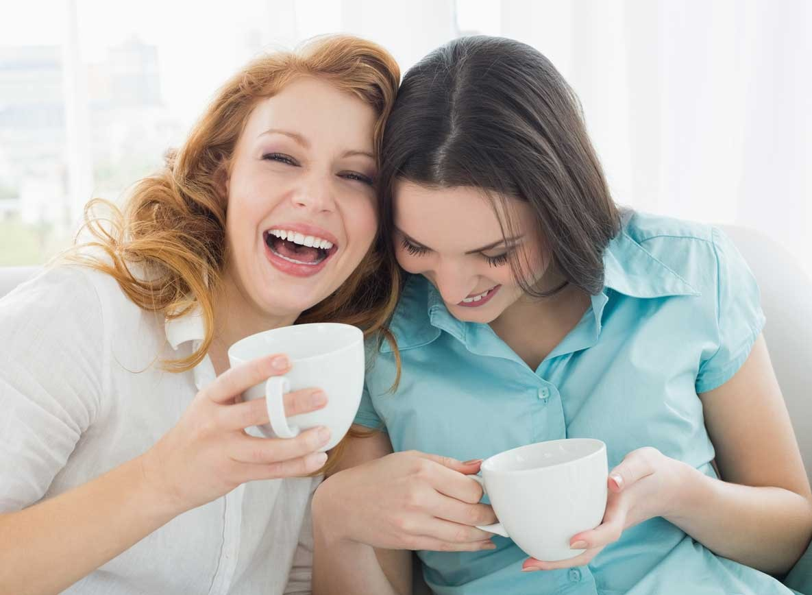 Two women laughing drinking out of mugs