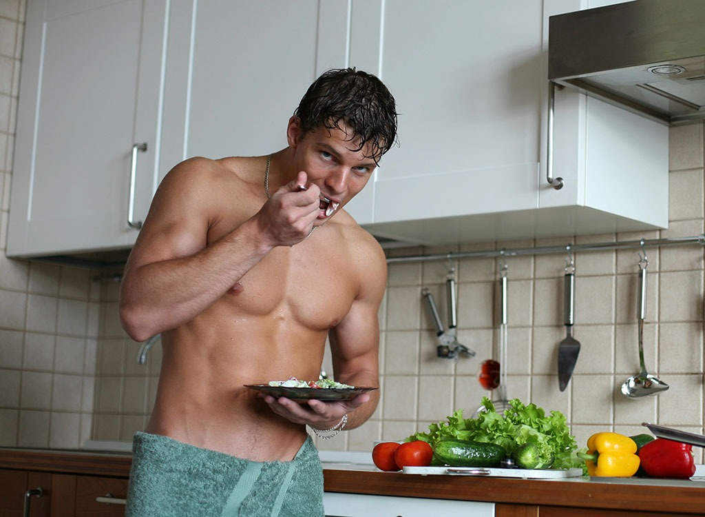 Man standing up eating from plate